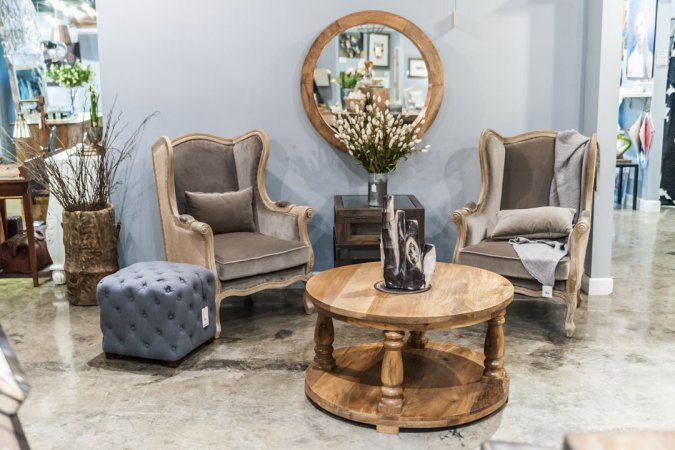 Highback, upholstered chairs and solid wood coffee table at Adjectives Altamonte